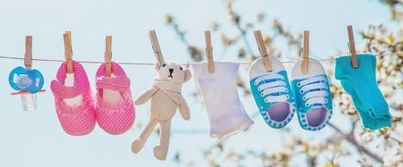Baby clothes and accessories weigh on the rope after washing in the open air. Selective focus. nature. Foto de archivo