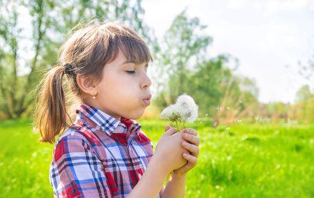 Child girl with dandelions in the park. Selective focus. Standard-Bild