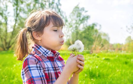 Child girl with dandelions in the park. Selective focus. Фото со стока