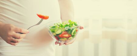A pregnant woman eats a salad with vegetables. Selective focus. Food. 免版税图像