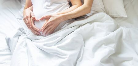 Pregnant woman with man hug belly in bed. Selective focus. people.
