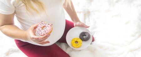 A pregnant woman eats sweet donuts. Selective Focus. Food.