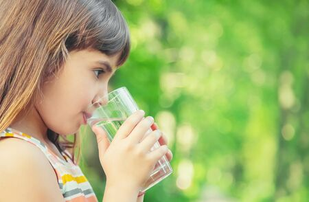 A child drinks water from a glass on the nature. Selective focus. Drink. Standard-Bild