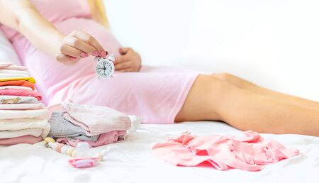 Pregnant woman with an alarm clock. Selective focus. people. Stock Photo