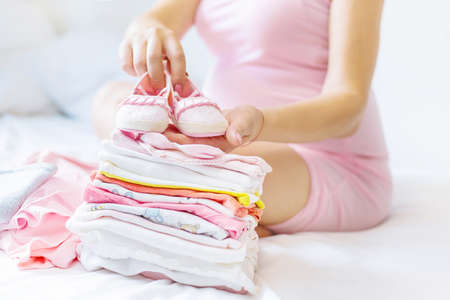 A pregnant woman is folding baby things. Selective focus. people. Standard-Bild