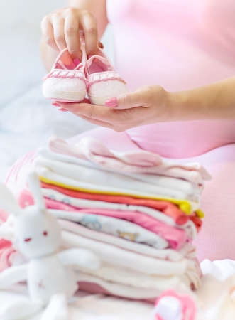 A pregnant woman is folding baby things. Selective focus. people. Reklamní fotografie