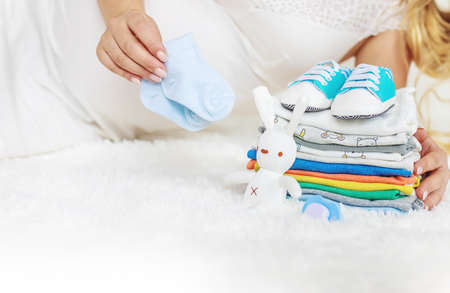 Baby clothes and a pregnant woman. Selective focus. people. Archivio Fotografico