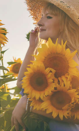 Woman in a field of sunflowers. Selective focus. nature. 스톡 콘텐츠 - 152406384