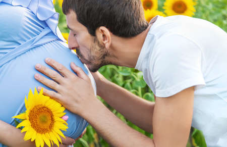 Pregnant woman and man in a field of sunflowers. Selective focus. nature. 스톡 콘텐츠 - 152296267