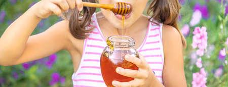 Child eats honey summer photo. Selective focus. nature. 스톡 콘텐츠 - 152423159