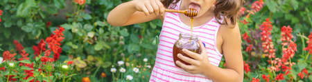 Child eats honey summer photo. Selective focus. nature. 스톡 콘텐츠 - 152422949