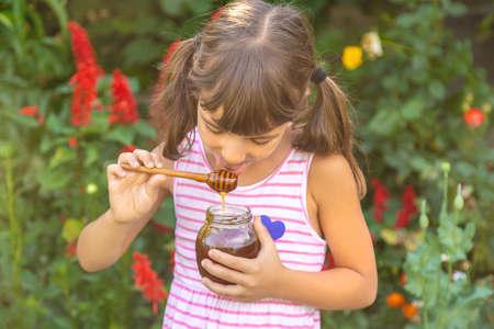 Child eats honey summer photo. Selective focus. nature. 스톡 콘텐츠 - 152424466