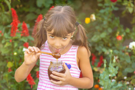 Child eats honey summer photo. Selective focus. nature. 스톡 콘텐츠 - 152424353