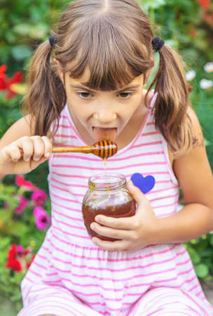 Child eats honey summer photo. Selective focus. nature. 스톡 콘텐츠 - 152423344