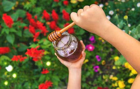 Child eats honey summer photo. Selective focus. nature.