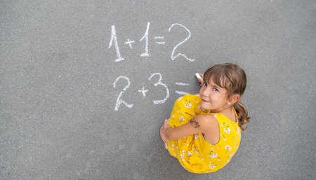 The child writes math on the pavement. Selective focus. summer. Archivio Fotografico