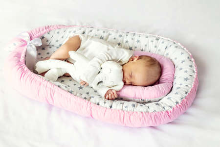 A newborn baby sleeps in a cocoon. Selective focus. People.