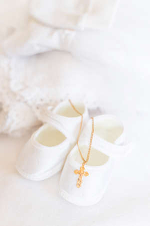 Clothes and a cross for the baby's christening. Selective focus. White.