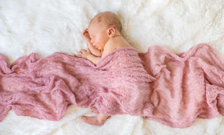 Newborn baby sleeping on a pink background. Selective focus. people.