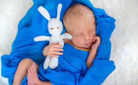 Newborn baby sleeping on a blue background. Selective focus. people. Standard-Bild