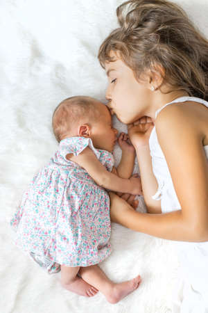 newborn toddler with older sister. selective focus. people.