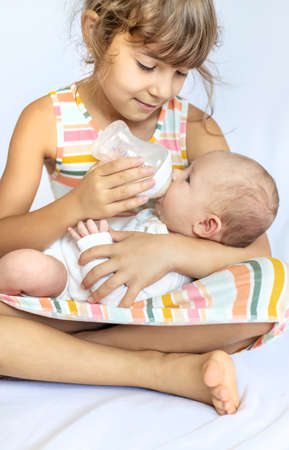 An older sister is feeding a newborn baby. Selective focus. People.