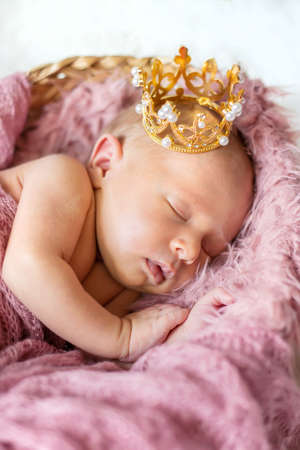 Newborn baby in a girl crown. Selective focus. people.
