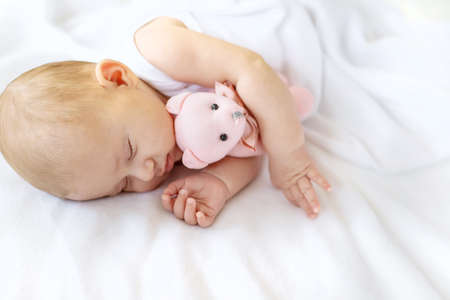 Baby sleeps with a teddy bear on a white background. Selective focus. People. Фото со стока