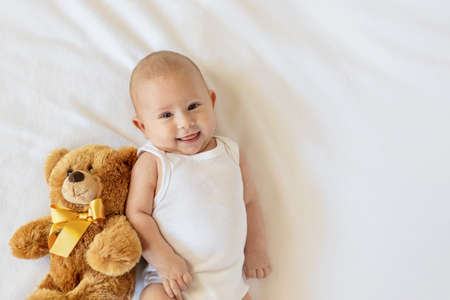 Baby plays with teddy bear against white background. Selective focus. People. Фото со стока