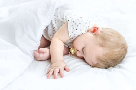 Baby sleeps on a white bed. Selective focus. Child. Foto de archivo