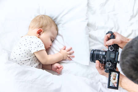 Baby sleeps on a white bed. father takes pictures, Selective focus. Child.