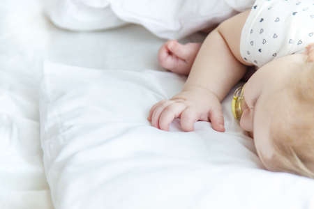 Baby sleeps on a white bed. Selective focus. Child.