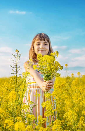 A child in a yellow field, mustard blooms. Selective focus ..