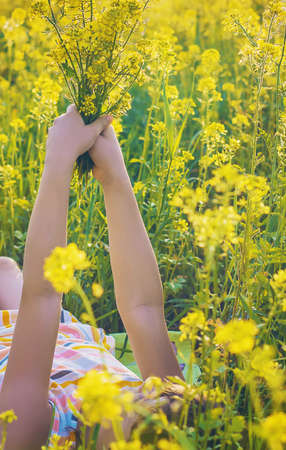 A child in a yellow field, mustard blooms. Selective focus. nature. 스톡 콘텐츠