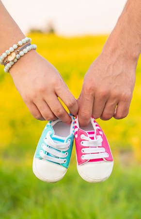 pregnant woman and man hold baby shoes. Selective focus. nature. 스톡 콘텐츠