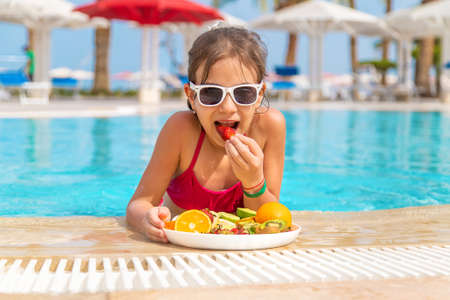 The child eats fruit near the pool. Selective focus. Kid.