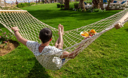 A man on a hammock with fruits. Selective focus. People.