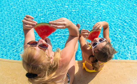 Mother and child eat watermelon near the pool. Selective focus. Food.