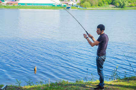 A man is fishing on the lake. Selective focus. Nature. Foto de archivo