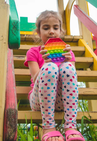 colorful antistress sensory toy fidget push pop it in child hands. Selective focus. nature.