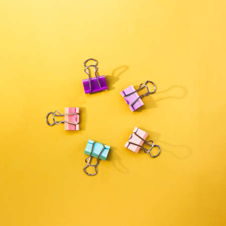 Five colorful paper clips forming circle on a yellow backdrop. Good stationery backgrop with space for text
