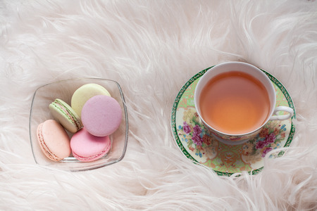 Macaroons and tea on white fur background Stock Photo