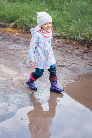 Little girl running to the puddle and smiling Stock Photo