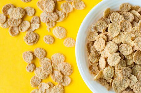Breakfast pouring milk into corn flakes creating splash apple and orange fruit cookies Imagens