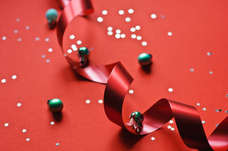 Red ribbon and glitter stars on a red background.