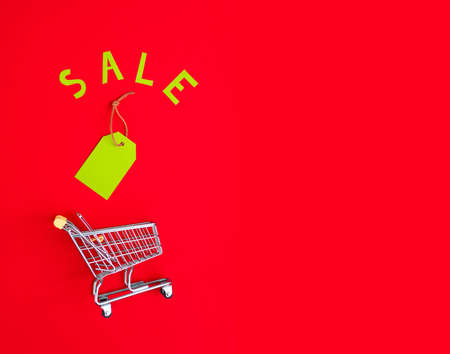close-up of shopping trolley on color background with some copy space. Black Friday. Shopping Price tags sale on a red background. view from above. Stock Photo