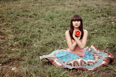 beautiful girl in a long skirt with grapefruits on the grass in the park Stock Photo - 9275860