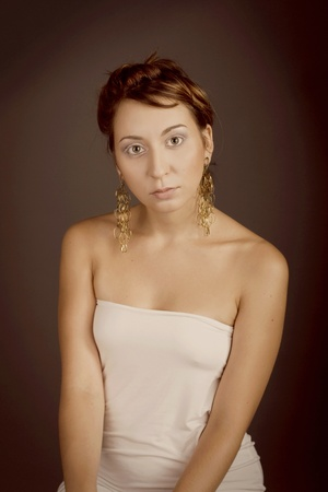 beautiful girl in a white dress with gold earrings photo