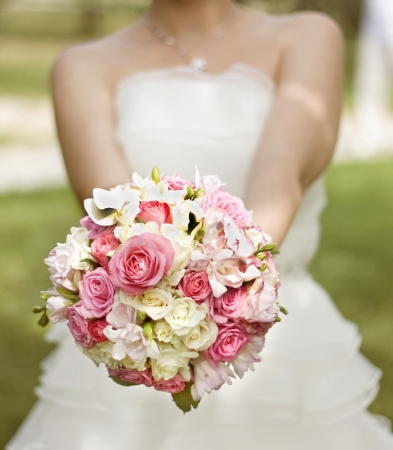 Bride in a white dress with a wedding bouquet of white and pink flowers photo
