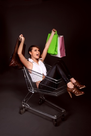 happy woman in the shopping cart with shopping bags photo